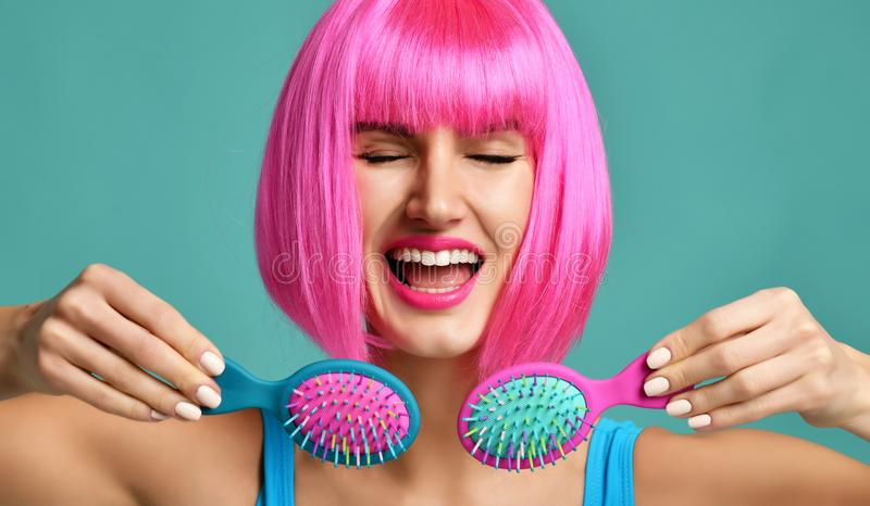 Closeup portrait of happy fashion brunette woman hold two small pink blue yellow small hair comb brush laughing in pink wig royalty free stock photo