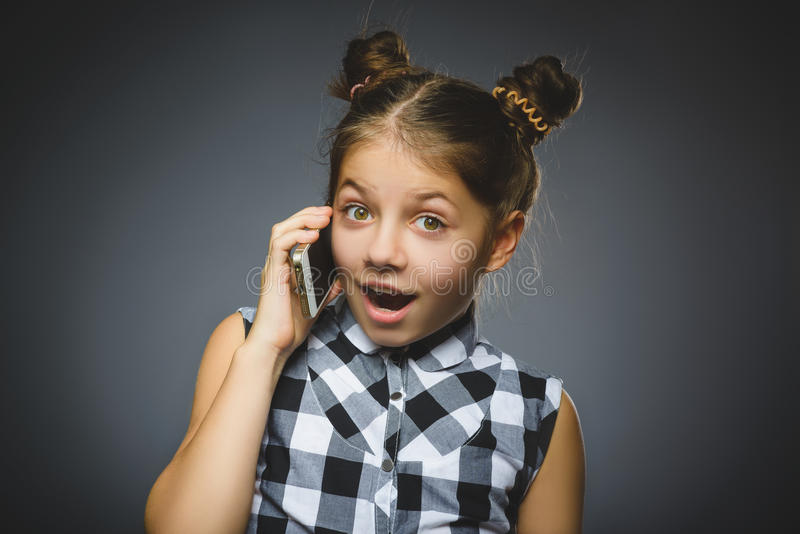 Closeup Portrait of happy girl with mobile or cell phone on gray background.  royalty free stock photography