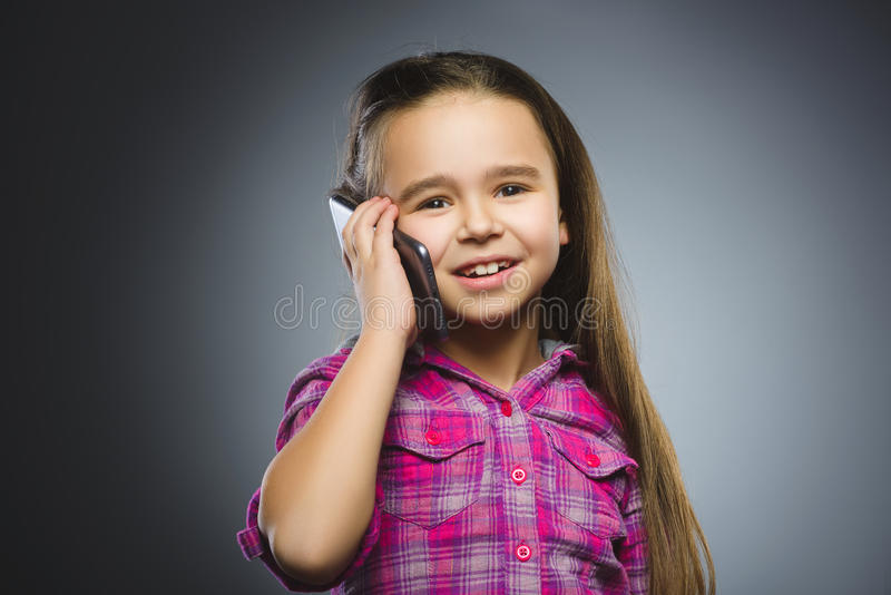 Closeup Portrait of happy girl with mobile or cell phone on gray background.  stock images