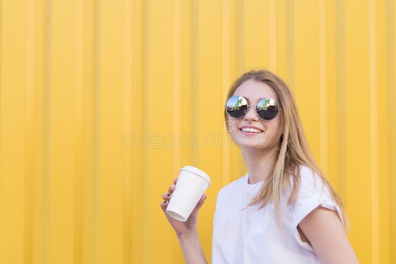 Closeup portrait of a happy girl standing on a yellow background with a paper cup of coffee in her arms and smiles royalty free stock photography
