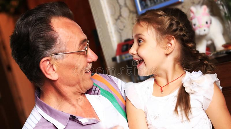Closeup.portrait of happy grandfather and granddaughter in the nursery stock photo