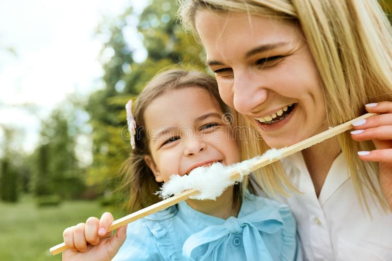 Closeup portrait of happy little girl having fun and eating cotton candy with her mother in the park. stock photos