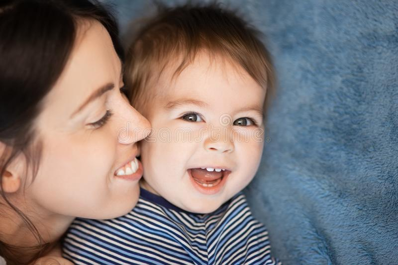 Mother and baby boy on bed. Closeup portrait of happy mother and her baby boy on bed royalty free stock images