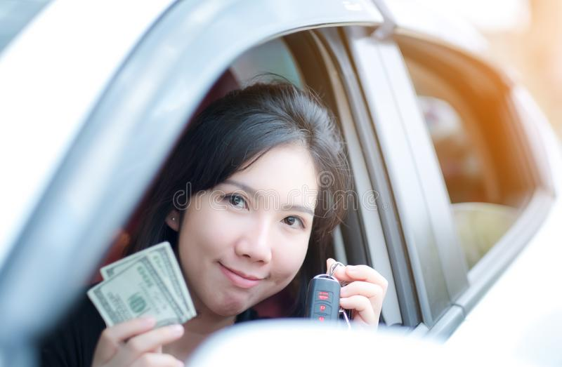 Closeup portrait happy smiling attractive asia woman sitting in her new white car showing keys, holding dollar  Personal stock images