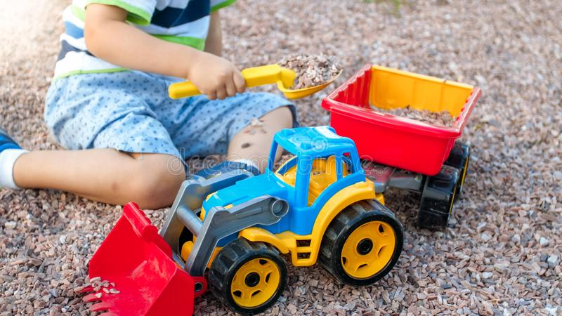 Closeup portrait of happy smiling 3 years old child boy digging sand on the playground with toy plastic truck or royalty free stock image