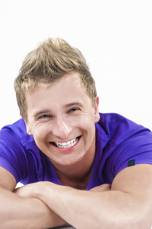 Closeup Portrait of Happy Smiling Young Caucasian Handsome Tanned Man Laying Down with Hands Folded in Front. royalty free stock photo