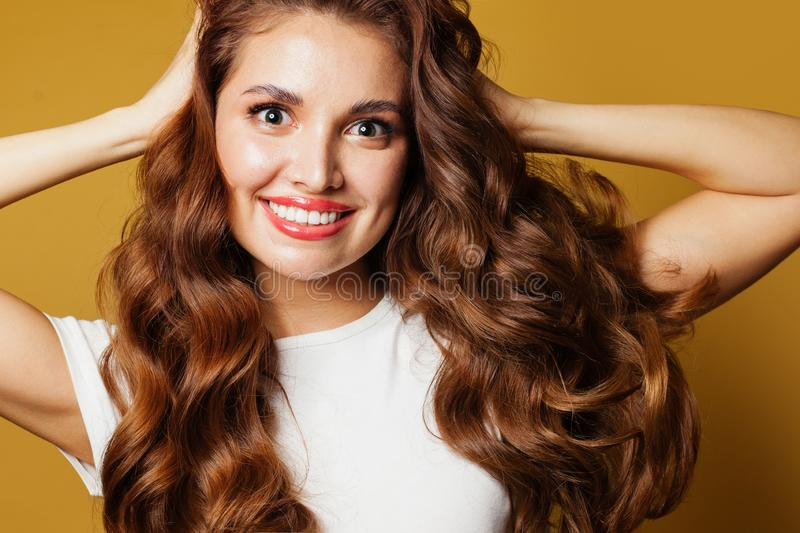 Closeup portrait of happy woman with natural makeup and brown curly hair. Pretty female face closeup stock photography
