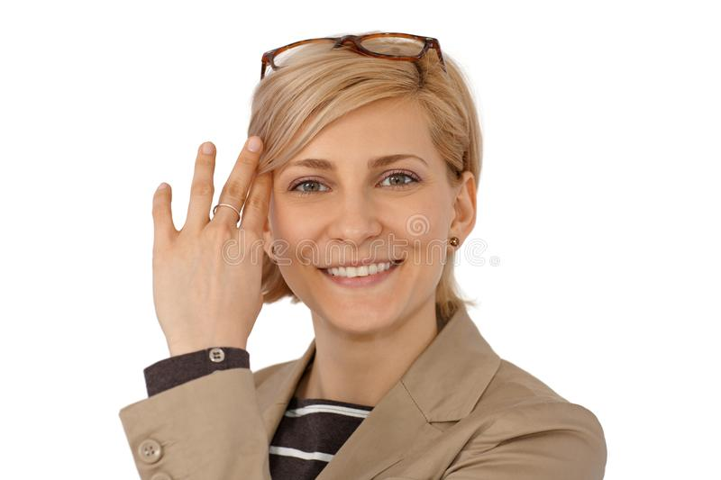 Closeup portrait of happy woman. Closeup portrait of happy young blonde woman smiling, looking at camera sweeping aside hair from face royalty free stock images