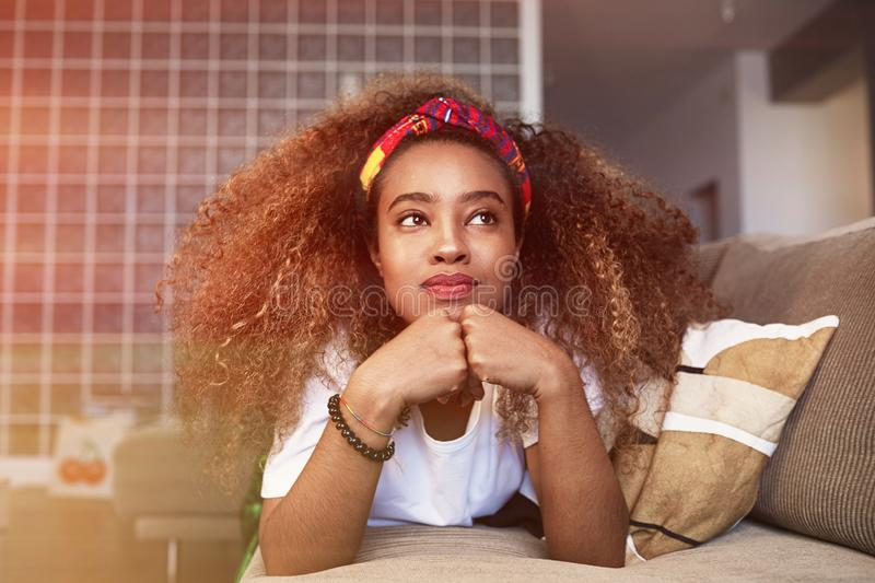 Closeup portrait of a happy young American African girl with long curly hair relaxing and have fun alone on sofa at royalty free stock photo