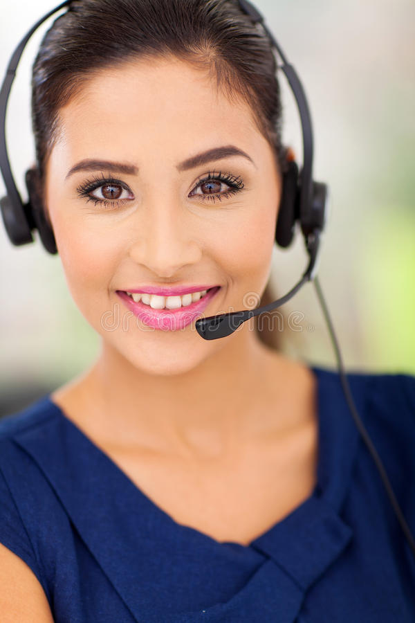 Call centre employee. Closeup portrait of a happy young call centre employee smiling with a headset royalty free stock image