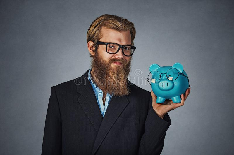 Man smiling holding Piggy bank both wearing glasses isolated on gray. Closeup portrait head shot young serious smiling happy hipster businessman holding Piggy royalty free stock photo