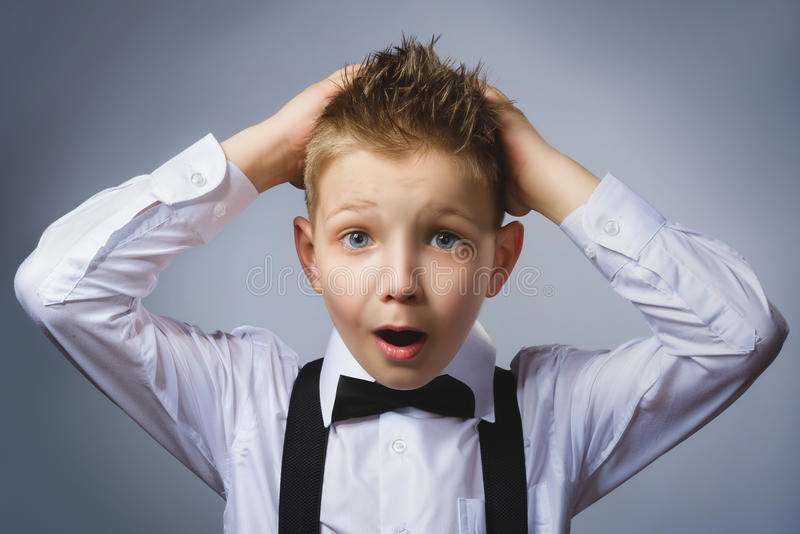 Closeup portrait headshot nervous anxious stressed afraid boy isolated grey background. Negative emotion facial. Expression stock photography