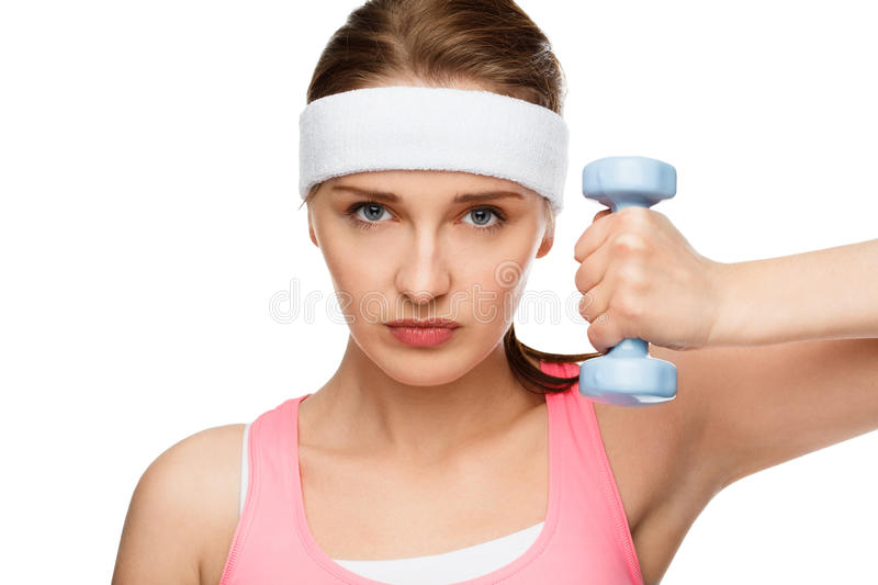 Closeup portrait healthy athletic woman lifting weights. Closeup portrait athletic woman in gym lifting weights royalty free stock photography