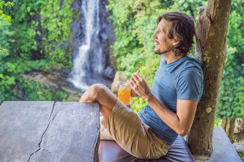 Closeup portrait image of a beautiful man drinking ice tea with feeling happy in green nature and waterfall garden stock photography