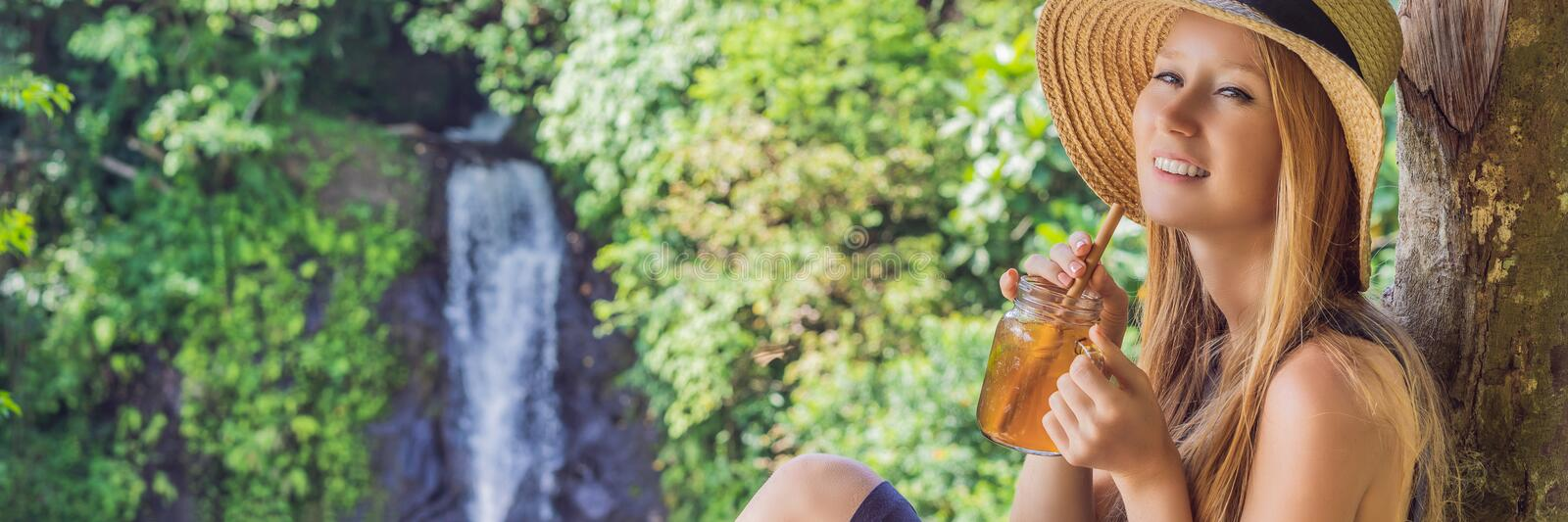 Closeup portrait image of a beautiful woman drinking ice tea with feeling happy in green nature and waterfall garden stock image