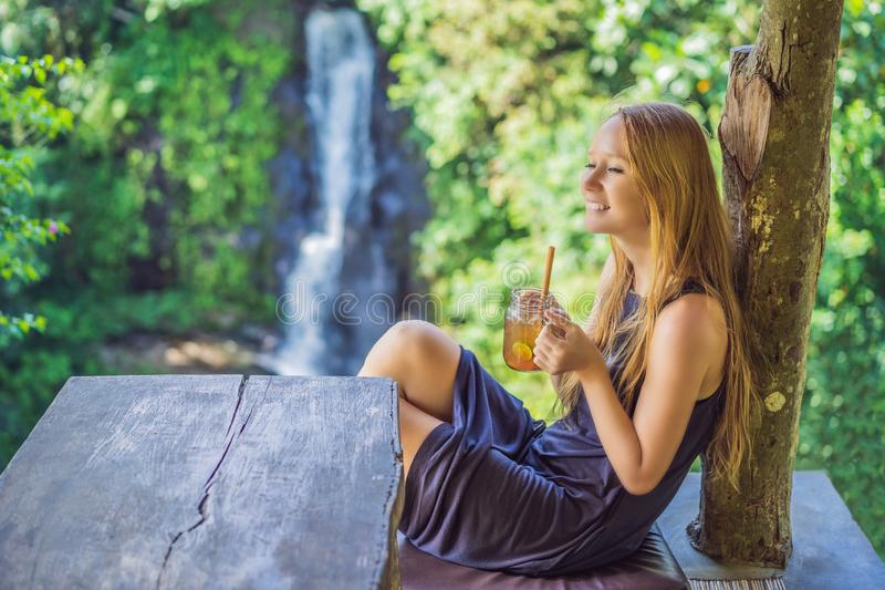 Closeup portrait image of a beautiful woman drinking ice tea with feeling happy in green nature and waterfall garden royalty free stock photos