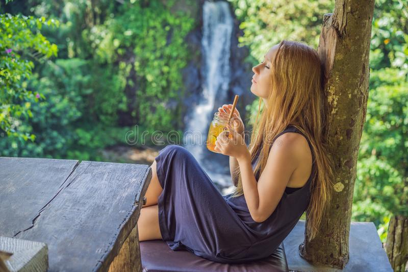 Closeup portrait image of a beautiful woman drinking ice tea with feeling happy in green nature and waterfall garden stock photography