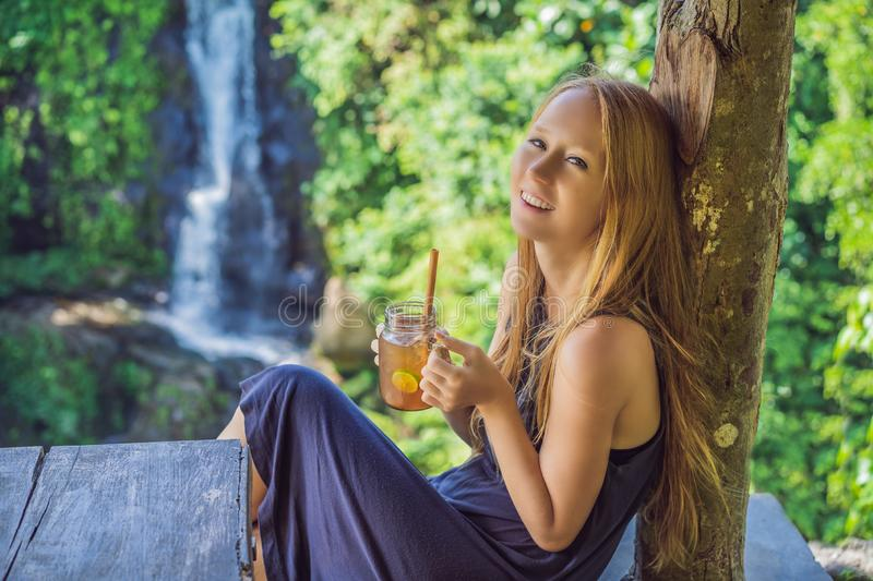 Closeup portrait image of a beautiful woman drinking ice tea with feeling happy in green nature and waterfall garden stock images
