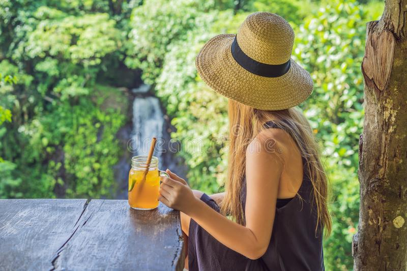 Closeup portrait image of a beautiful woman drinking ice tea with feeling happy in green nature and waterfall garden stock photos