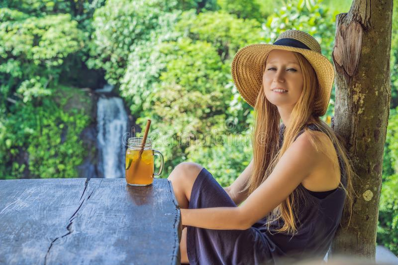 Closeup portrait image of a beautiful woman drinking ice tea with feeling happy in green nature and waterfall garden royalty free stock image