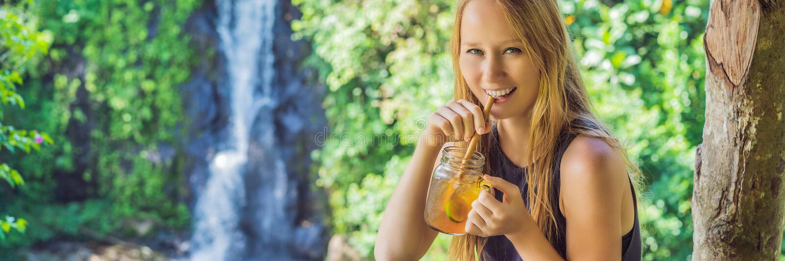 Closeup portrait image of a beautiful woman drinking ice tea with feeling happy in green nature and waterfall garden stock photo