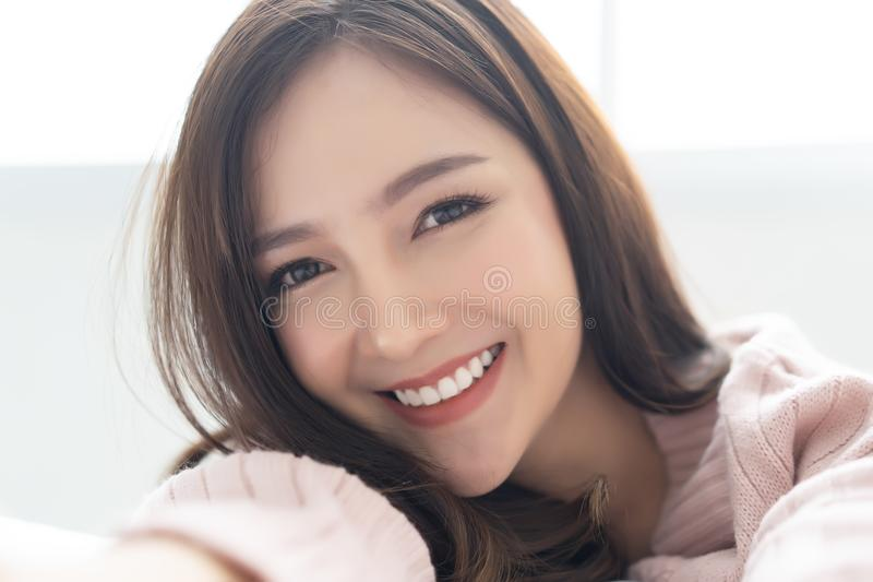 Closeup portrait of inspired caucasian Asian lady wearing knitted sweater pink cold smilling and taking selfie at her. Home.Concept woman lifestyle and winter royalty free stock photography