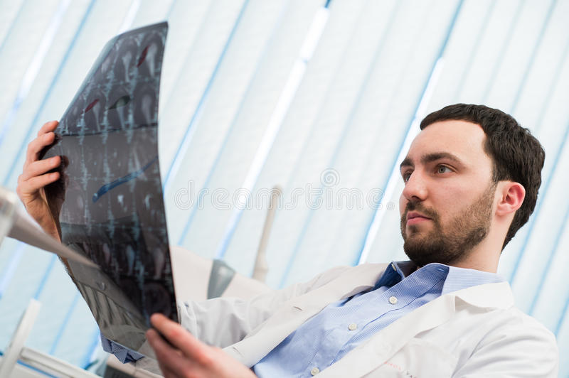 Closeup portrait of intellectual man healthcare personnel with white labcoat, looking at brain x-ray radiographic image stock photo