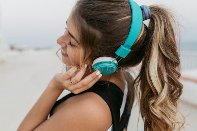 Closeup portrait joyful amazing woman in sportswear, with long curly hair listening to music through blue headphones royalty free stock photo
