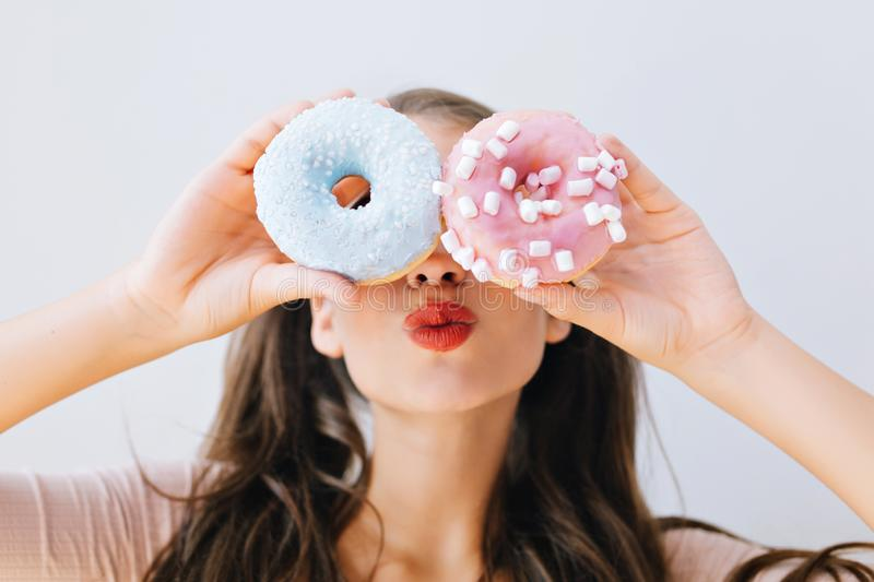 Closeup portrait joyful girl with red lips having fun with colorful donuts against her eyes. Attractive young woman with royalty free stock image