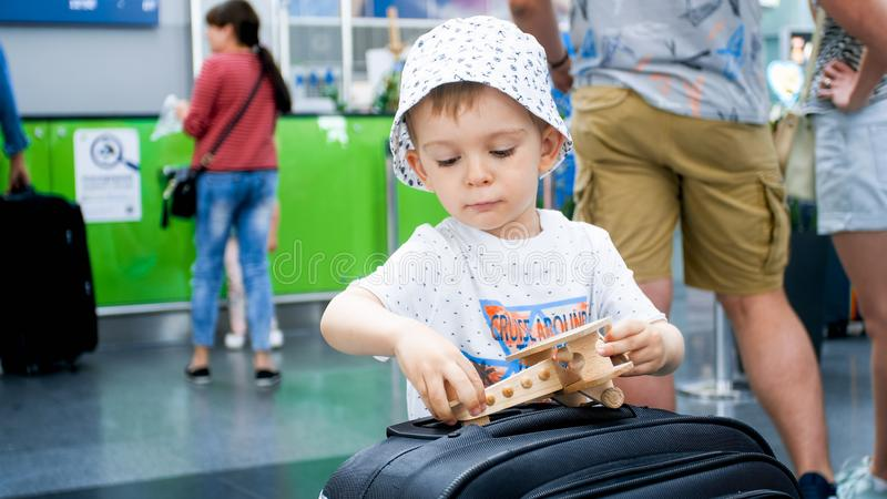 Closeup portrait of little boy holding and playing with miniature wooden airplane. Child traveling. Young tourist. stock photography