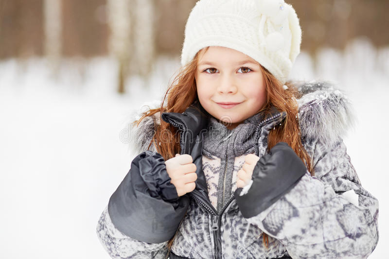 Closeup portrait of little girl in grey jacket with fur collar royalty free stock photography
