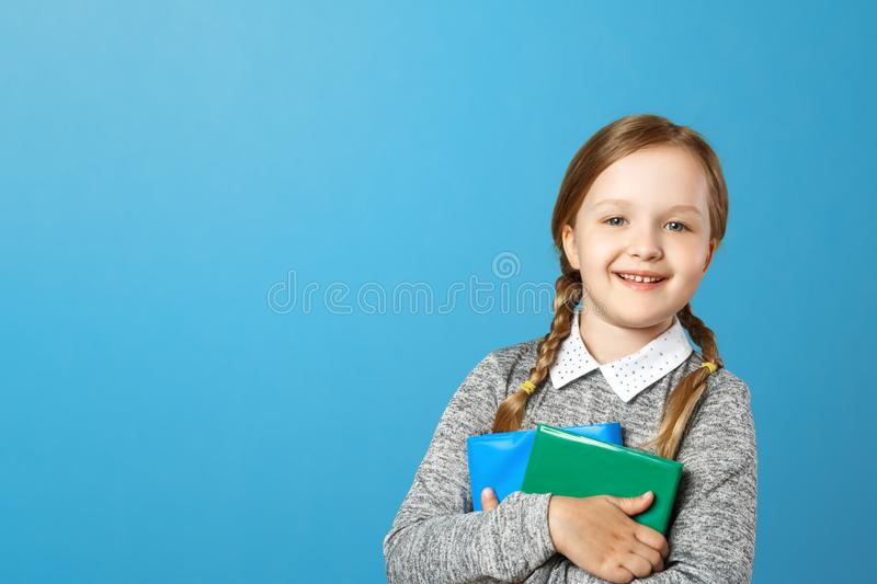 Closeup portrait of a little girl schoolgirl on a blue background. The child holds books. The concept of education and school. Copy space royalty free stock photo