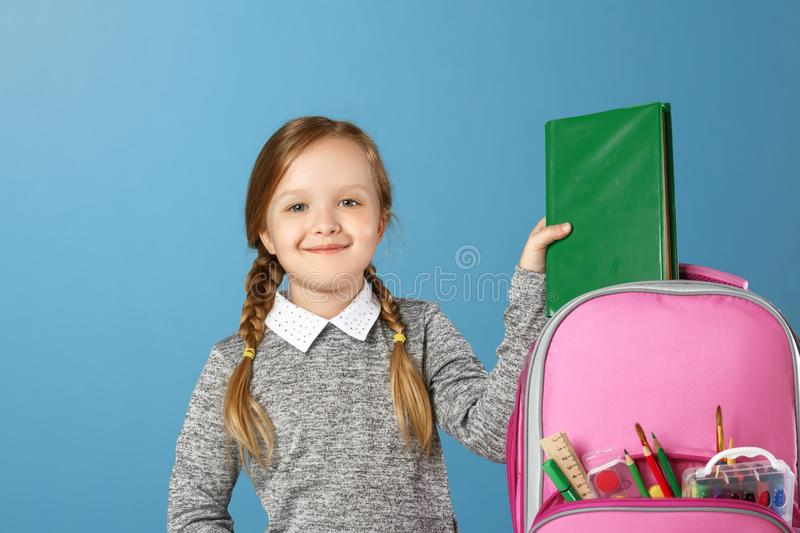 Closeup portrait of little girl schoolgirl on blue background. The child puts in a satchel book. Back to school. The concept of stock photo
