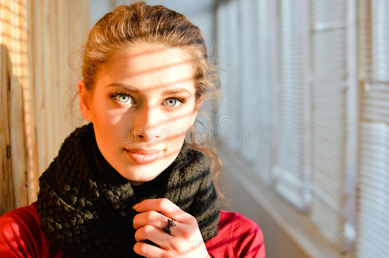 Closeup portrait on looking at camera wonderful beautiful young woman with blue eyes in shawl on a balcony window background stock image
