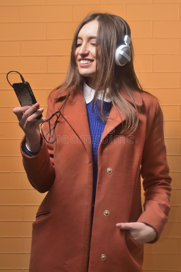 Closeup portrait of lovely young woman enjoying music using headphones, isolated over orange royalty free stock image