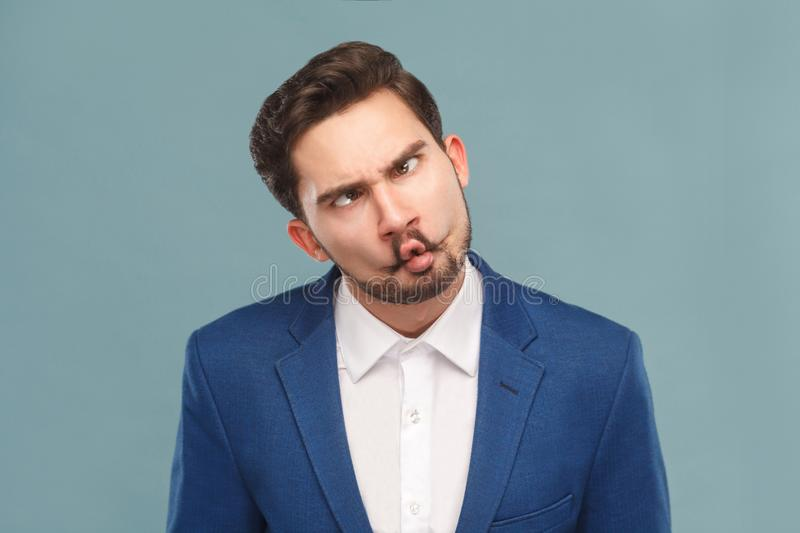 Closeup portrait of man with funny stupid mimicry face. Business people concept, richly and success. Indoor, studio shot on light blue background stock photo