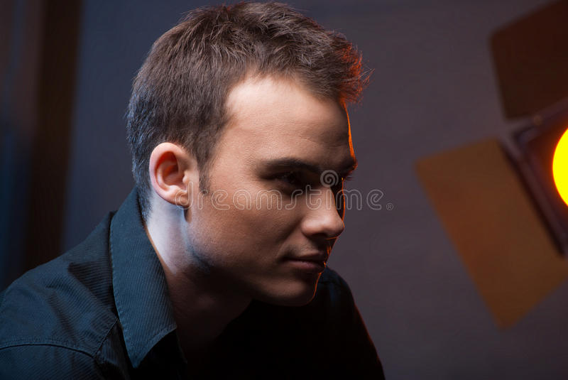 Closeup portrait of man in studio with flashes. Closeup portrait of a male model in studio on dark grey background with flashes royalty free stock photography