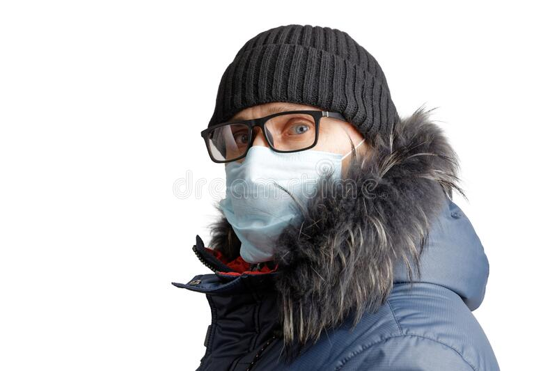 Closeup portrait of a man in winter clothes, black hat, glasses and a protective mask. stock photography