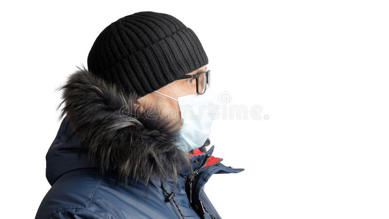Closeup portrait of a man in winter clothes, black hat, glasses and a protective mask. Isolated on white stock image