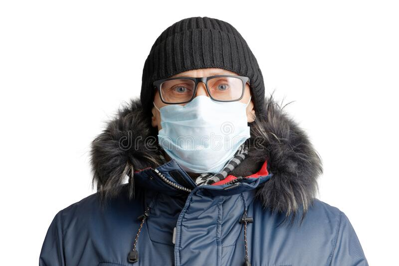 Closeup portrait of a man in winter clothes and a hat, glasses and a protective mask stock image