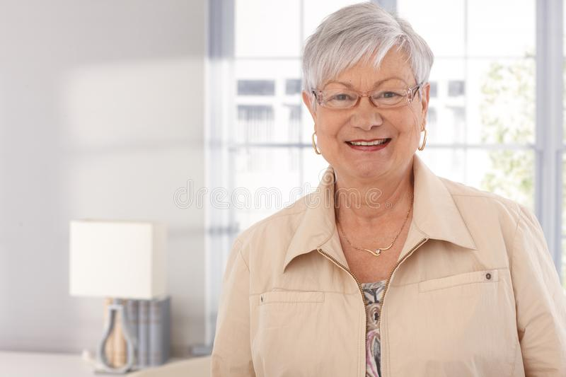 Closeup portrait of mature woman. Smiling happy, looking at camera royalty free stock image