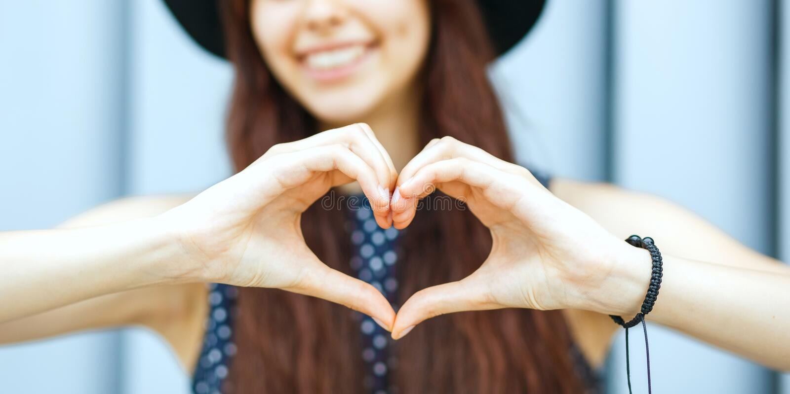 Closeup portrait of merry brunette model in hat making heart shape with her hands stock image