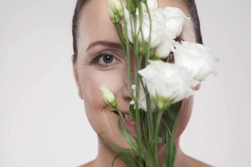 Closeup portrait of middle aged beautiful woman with perfect skin and wrinkles are hiding face with flowers. Skin Care Concept, royalty free stock photo