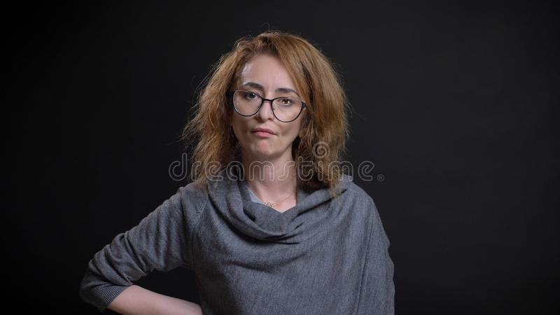 Closeup portrait of middle-aged extravagant redhead female in glasses being angry and furious and having hand on a hip royalty free stock photos