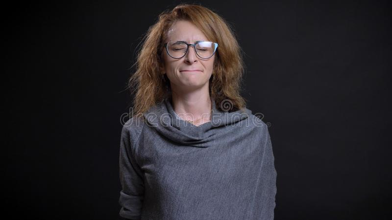Closeup portrait of middle-aged extravagant redhead female in glasses being depressed and sad in front of the camera stock image