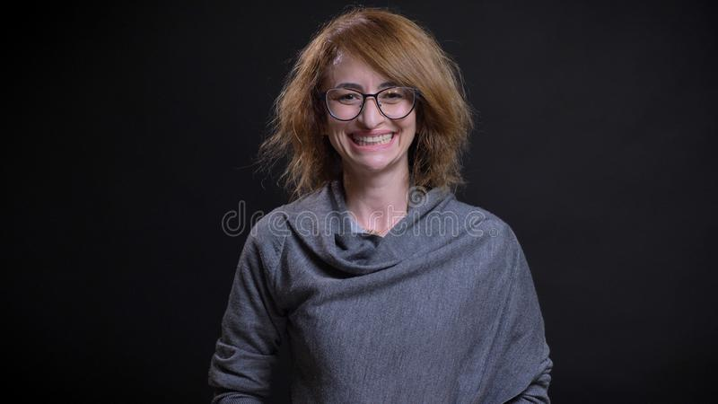 Closeup portrait of middle-aged extravagant redhead female in glasses being happy and smiling cheerfully while looking stock images