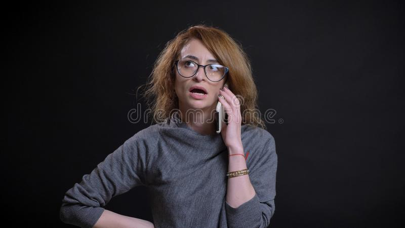 Closeup portrait of middle-aged extravagant redhead female in glasses having a casual conversation on the phone in front royalty free stock photo