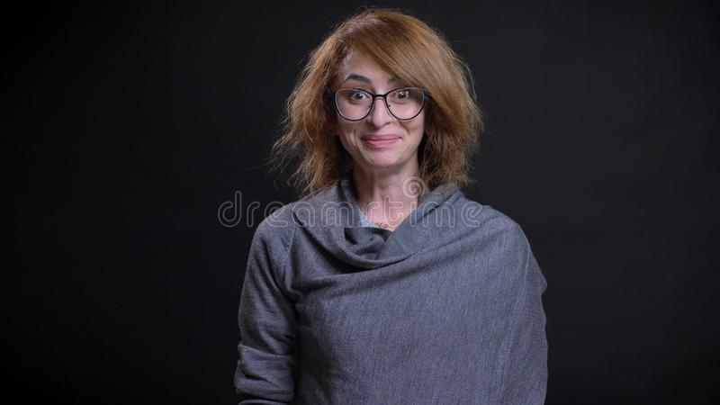 Closeup portrait of middle-aged extravagant redhead female in glasses smiling with excitement and happiness while stock image
