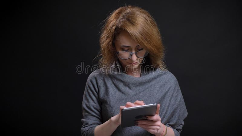 Closeup portrait of middle-aged extravagant redhead female in glasses texting on the tablet in front of the camera with stock images