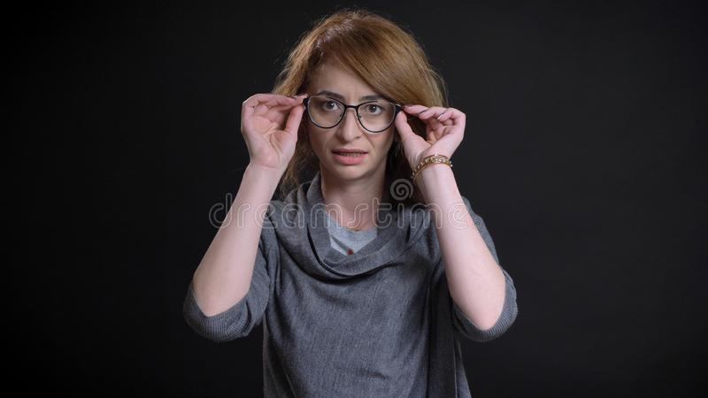 Closeup portrait of middle-aged extravagant redhead female looking straight at camera fixing her glasses with background royalty free stock photos